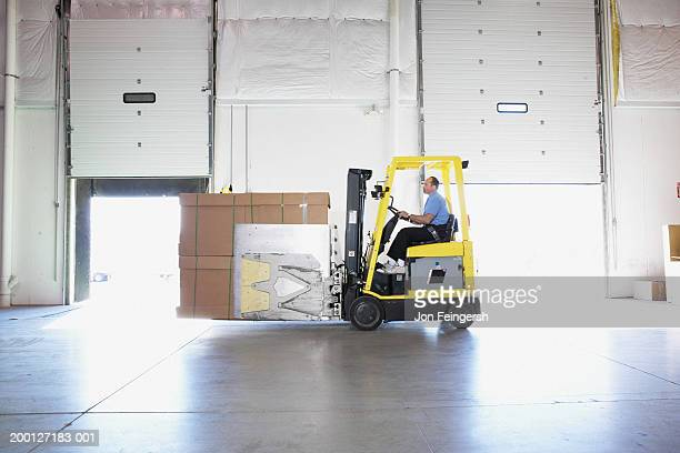man driving squeeze with boxes through warehouse, side view - industrial door stock pictures, royalty-free photos & images