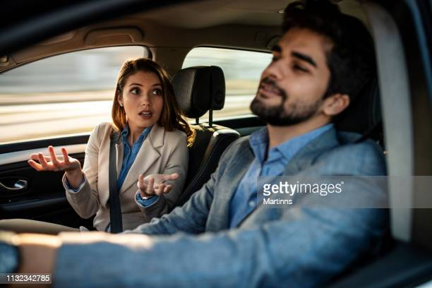a man driving while a female passenger is fussing about - fighting stock pictures, royalty-free photos & images