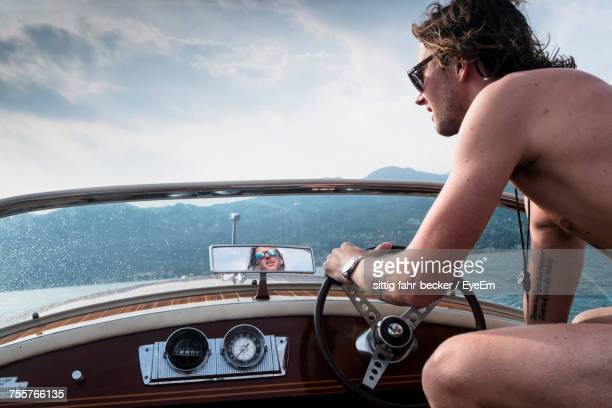 Man Driving Yacht Against Sky