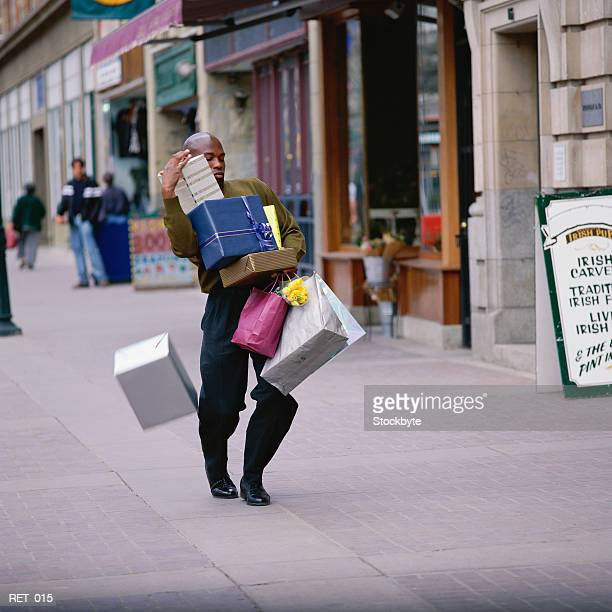 Man dropping box, carrying pile of presents and shopping bags