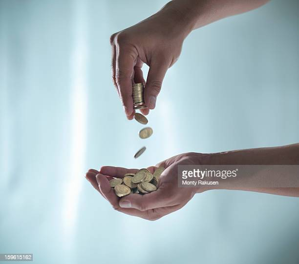 Man dropping pound coins into palm of hand, pounds sterling