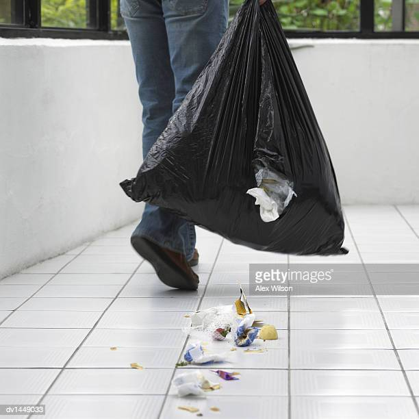 Man Dropping Rubbish on a Tiled Floor From a Hole in a Bin Bag