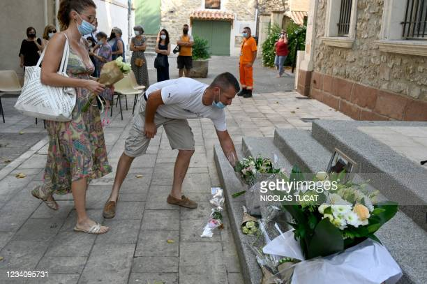 Man drops flowers during a ceremony in Le Plan-de-la-Tour, southeastern France on July 21 to pay a tribute to Doriane, a young woman who was...