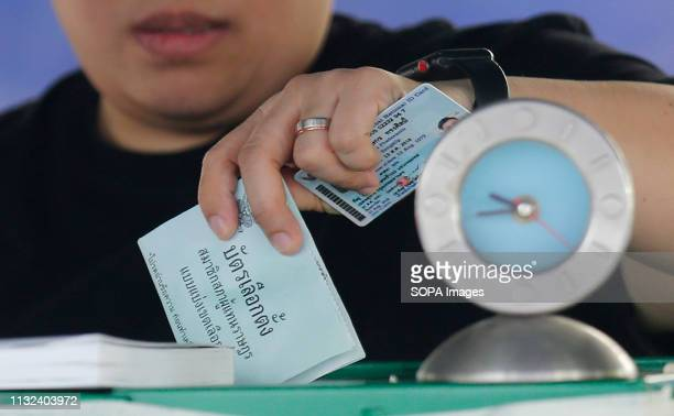 A man drops his vote into a ballot box during Thailand's general election in Bangkok