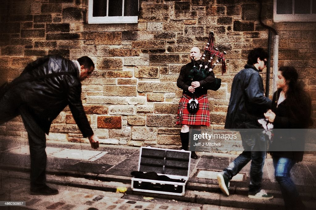 A man drops some money into a pipers case busking on the Royal Mile on April 23, 2014 in Edinburgh, Scotland. A referendum on whether Scotland should be an independent country will take place on September 18, 2014.