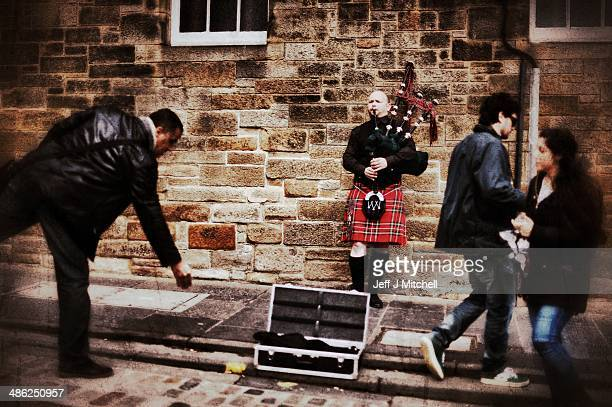 A man drops some money into a pipers case busking on the Royal Mile on April 23 2014 in Edinburgh Scotland A referendum on whether Scotland should be...