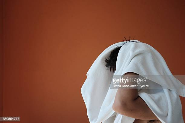 man drying hair with towel against brown wall - drying stock pictures, royalty-free photos & images