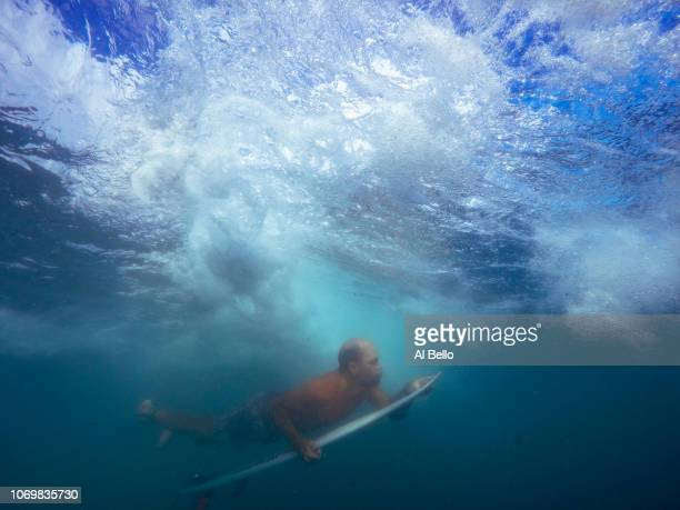 A man duck dives a wave on his surf board at Aviones Beach on November 16 2018 in Pinones Puerto Rico The beach flooded the town of Pinones and all...
