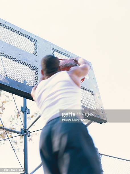 man dunking basketball, low angle view - shooting baskets stock photos and pictures