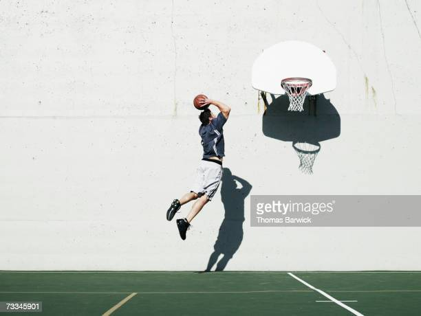 Man dunking basketball on outdoor court, mid-air, rear view