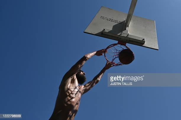 Man dunks the ball as he plays basketball in the hot weather in London Fields park in east London on June 25, 2020. - Just days after lockdown ended...