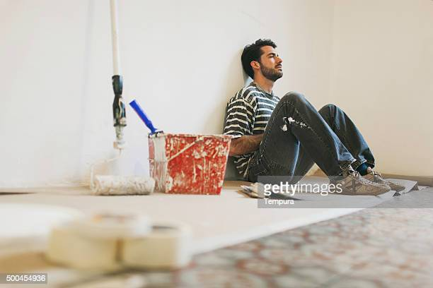 Man during a break while painting apartment.