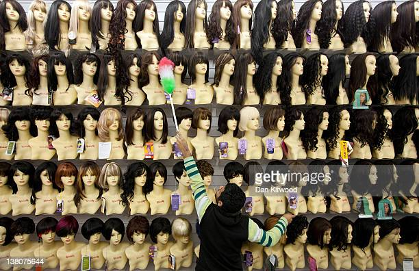 A man dusts shop mannequins displaying wigs in a hair and beauty store in Brixton on February 2 2012 in London England The hair and beauty sector has...