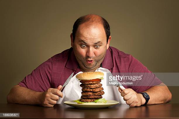 Man eating a burger with six patties