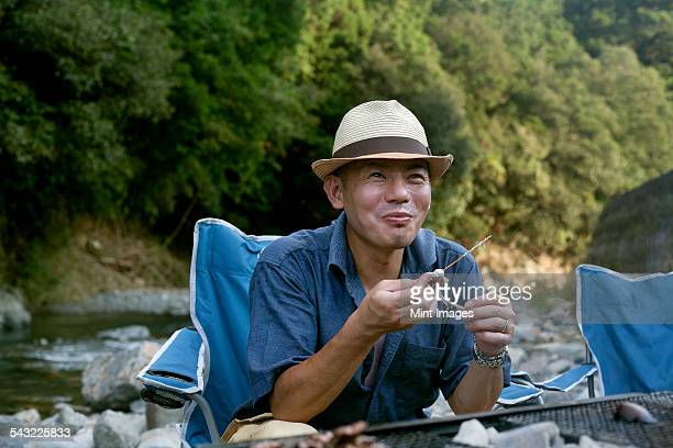 Man eating a grilled fish at a picnic.