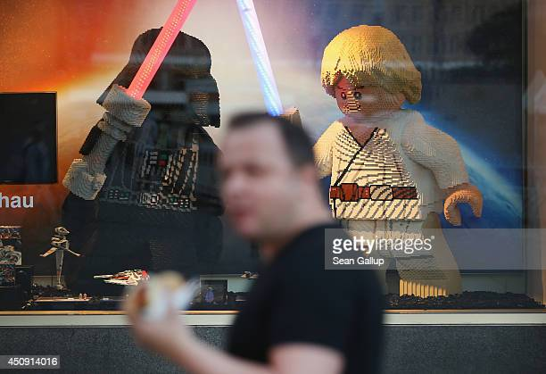 A man eating a hotdog walks past giant Star Wars figures made from Legos in the display window of a department store at Alexanderplatz on June 12...