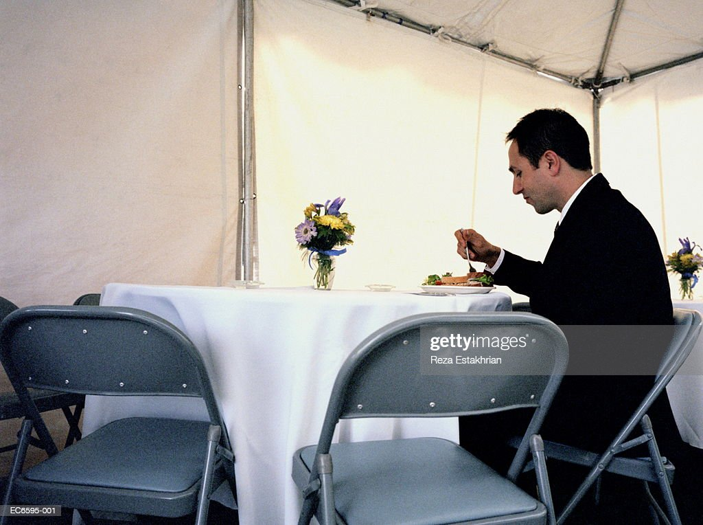 Man eating alone in banquet tent  Stock Photo  sc 1 st  Getty images & Man Eating Alone In Banquet Tent Stock Photo | Getty Images