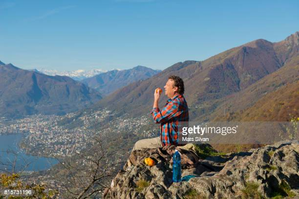 Man Eating an Apple on a Mountain Top