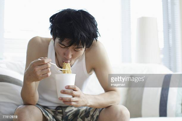 Man Eating an Instant Chinese Noodles Soup