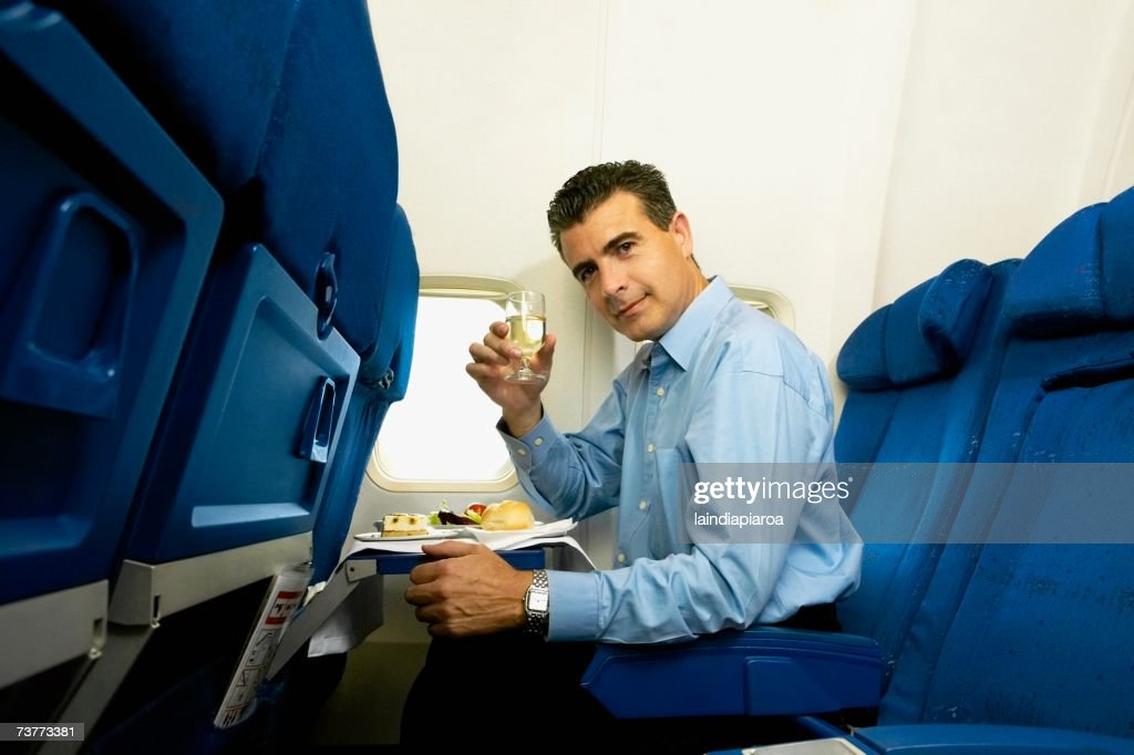 Man eating and toasting with wine on airplane : Stock Photo