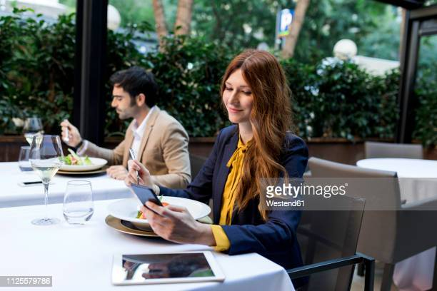 man eating and woman using cell phone in a restaurant - lunch break stock photos and pictures