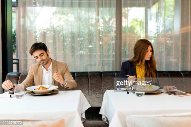 man eating and woman using tablet in a restaurant - 隣り合わせ ストックフォトと画像