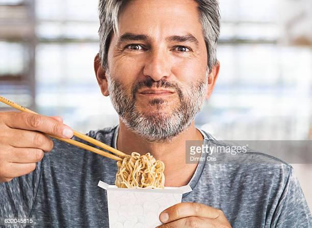 Man eating asian food with chopsticks