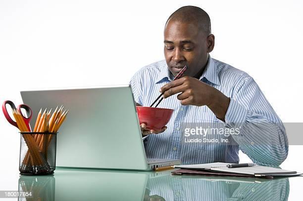Man eating Asian noodles at work