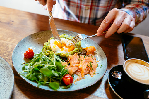 Man eating avocado toast with egg, salmon and arugula salad for brunch at the restaurant - gettyimageskorea