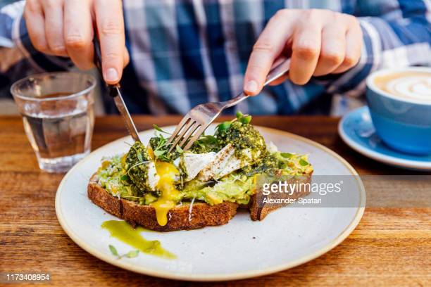 man eating avocado toast with poached egg, close up - vegetarianism stock pictures, royalty-free photos & images