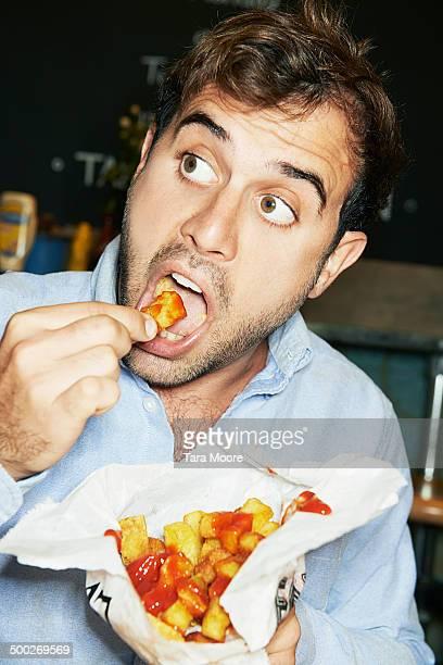 man eating bag of chips - abbuffata foto e immagini stock