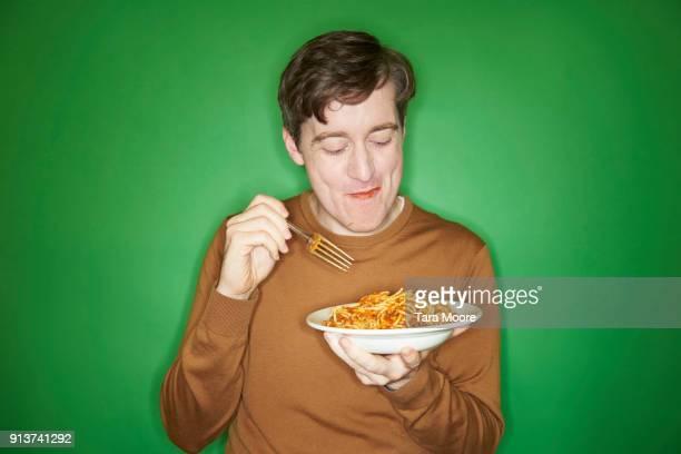 man eating bowl of pasta