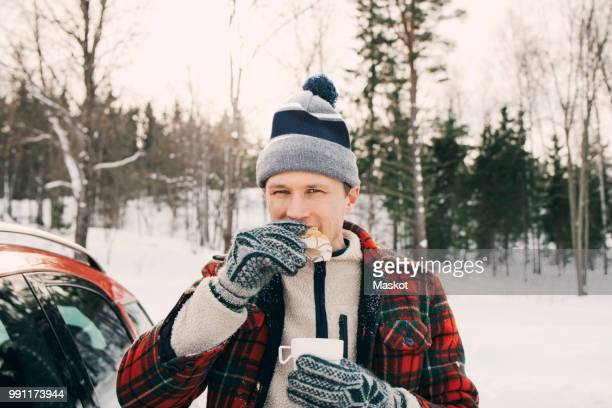 man eating bread while having coffee in car trunk at park during winter - warme dranken stockfoto's en -beelden