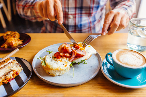 Man eating breakfast with egg, bacon, arugula on brioche bun and coffee - gettyimageskorea