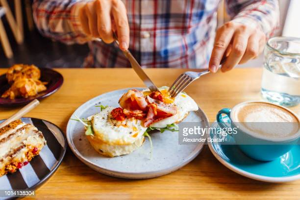 Man eating breakfast with egg, bacon, arugula on brioche bun and coffee