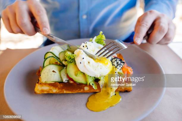 man eating brunch with waffle, avocado, salmon and poached egg with liquid egg yolk - savory food stock pictures, royalty-free photos & images