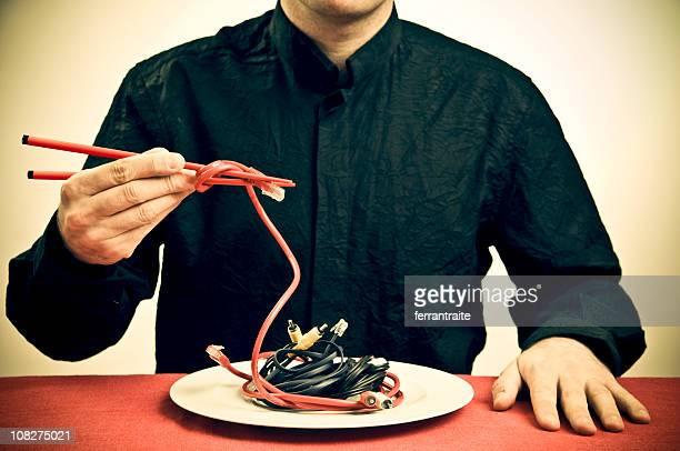 Mann Essen mit Stäbchen, goldfarbenem Kabel