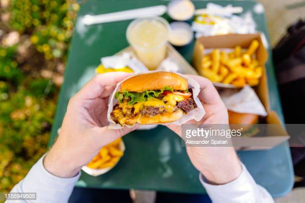 man eating cheeseburger, personal perspective view - unhealthy living stock pictures, royalty-free photos & images
