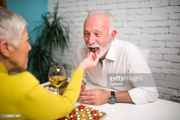 man eating chocolate from wife's hand - couple chocolate stock pictures, royalty-free photos & images