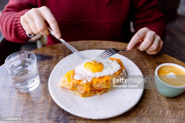 man eating croque madame sandwich with cheese and fried egg - breakfast stock pictures, royalty-free photos & images
