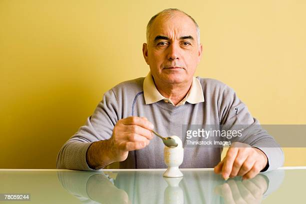 man eating egg - hard boiled eggs stock photos and pictures