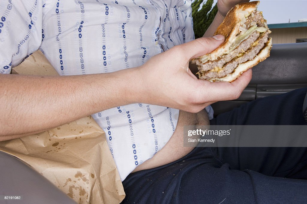 Man eating fast food in his car : Stock Photo