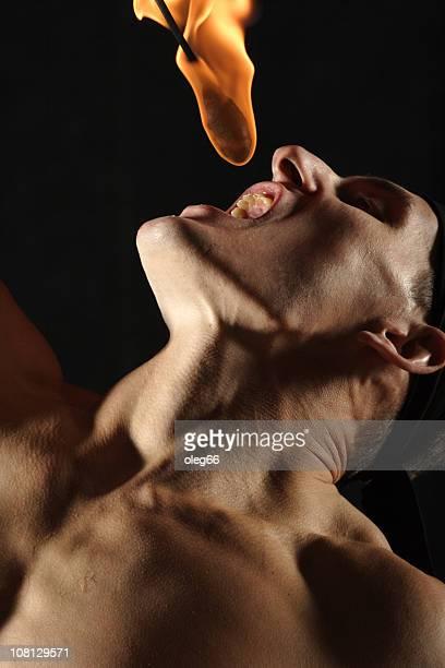 hombre comiendo fuego linterna - faquir fotografías e imágenes de stock