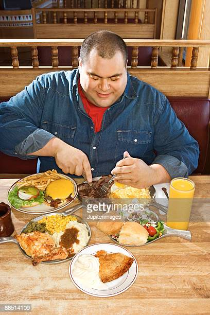 Man eating from multiple plates of food in restaurant