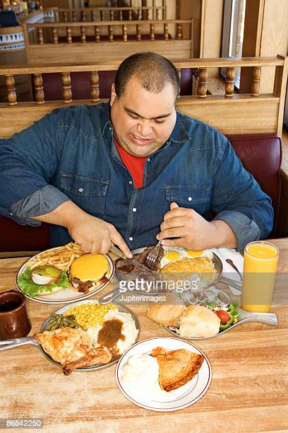 Man eating from multiple plates of food