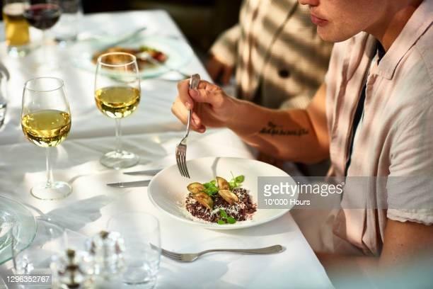 man eating gourmet food in restaurant - ブラッスリー ストックフォトと画像