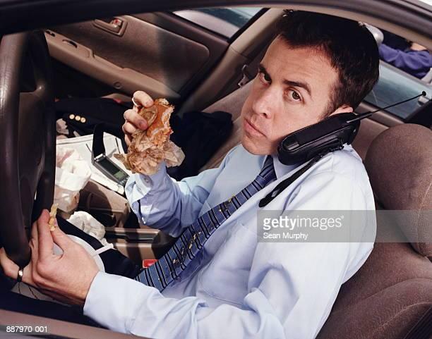 Man eating hamburger and using mobile phone whilst driving car