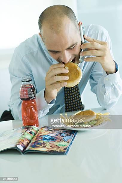 'Man eating hamburgers, using cell phone, and looking at comic book'