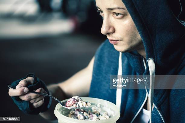 man eating healthy snack in gym - nut food stock photos and pictures