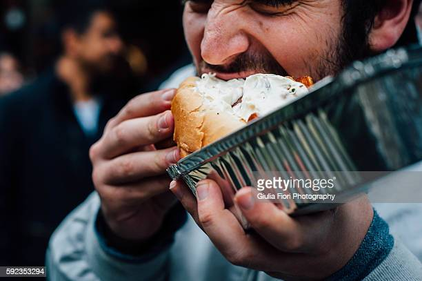 man eating hot dog on the streets - street food stock pictures, royalty-free photos & images
